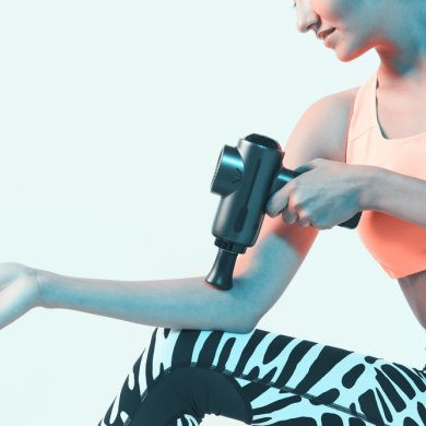 Athletic young female massaging hand by handheld massage gun, post-workout recovery routines, close up